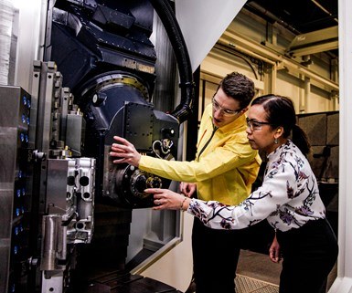 Two people looking inside a machine tool
