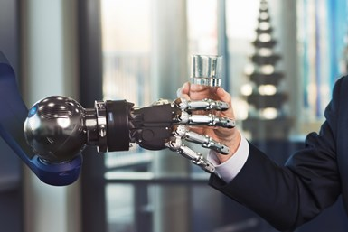 Five-fingered robot gripper handing a person a glass of water