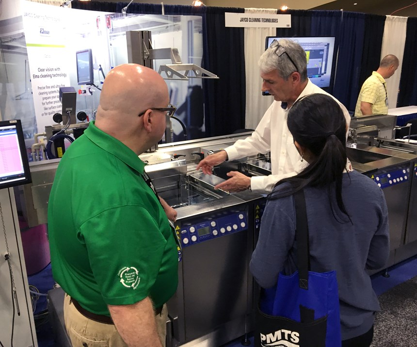 man in company booth showing attendees cleaning equipment