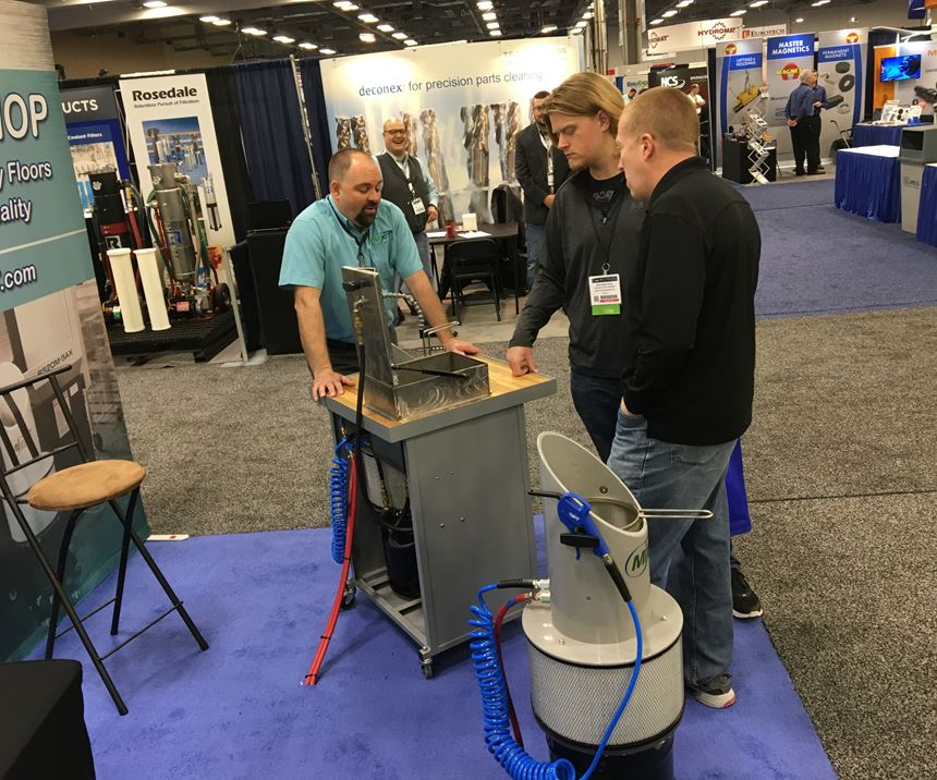 man in company booth showing cleaning equipment to attendees