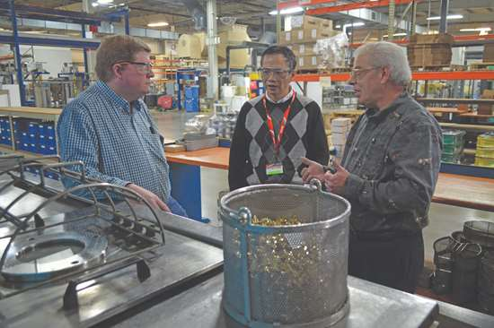 Electro-Spec and BHC employees stand around vacuum vapor degreasing machine