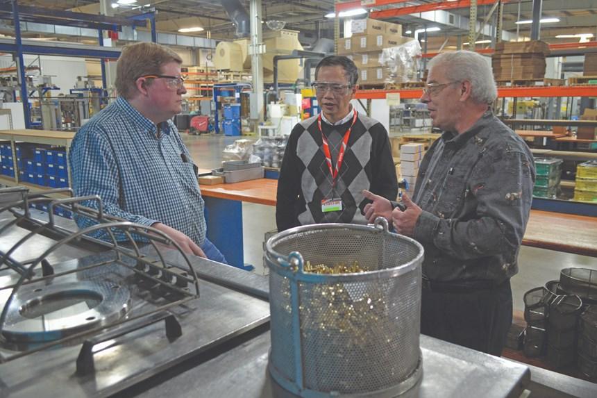 Electro-Spec and BHC employees stand around vacuum vapor degreasing machine
