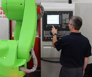 An employee stands next to a cobot at a machine tool