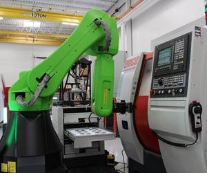 An employee stands next to a cobot at a machine tool