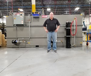 Rod Anthony standing in front of the PRAB oil recycling system