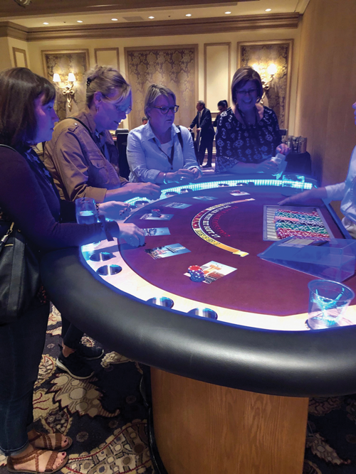 people standing around blackjack table at casino