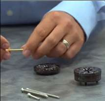 man's hands holding screw and collets sitting on table