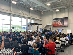 Attendees sitting at TMA's Precision Machining Competition, watching the big screen