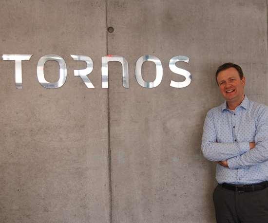 Daniel Maerklin standing next to Tornos logo on wall