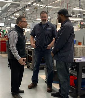 Michael Tamasi (left), stands with other AccuRounds employees on shop floor