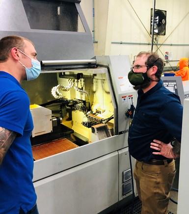 two men conversing at Swiss machine