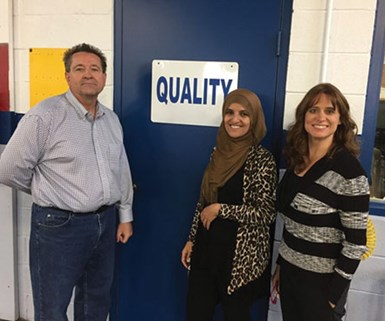 """Aneesa Muthana with coworkers standing next to a door that reads """"Quality"""""""