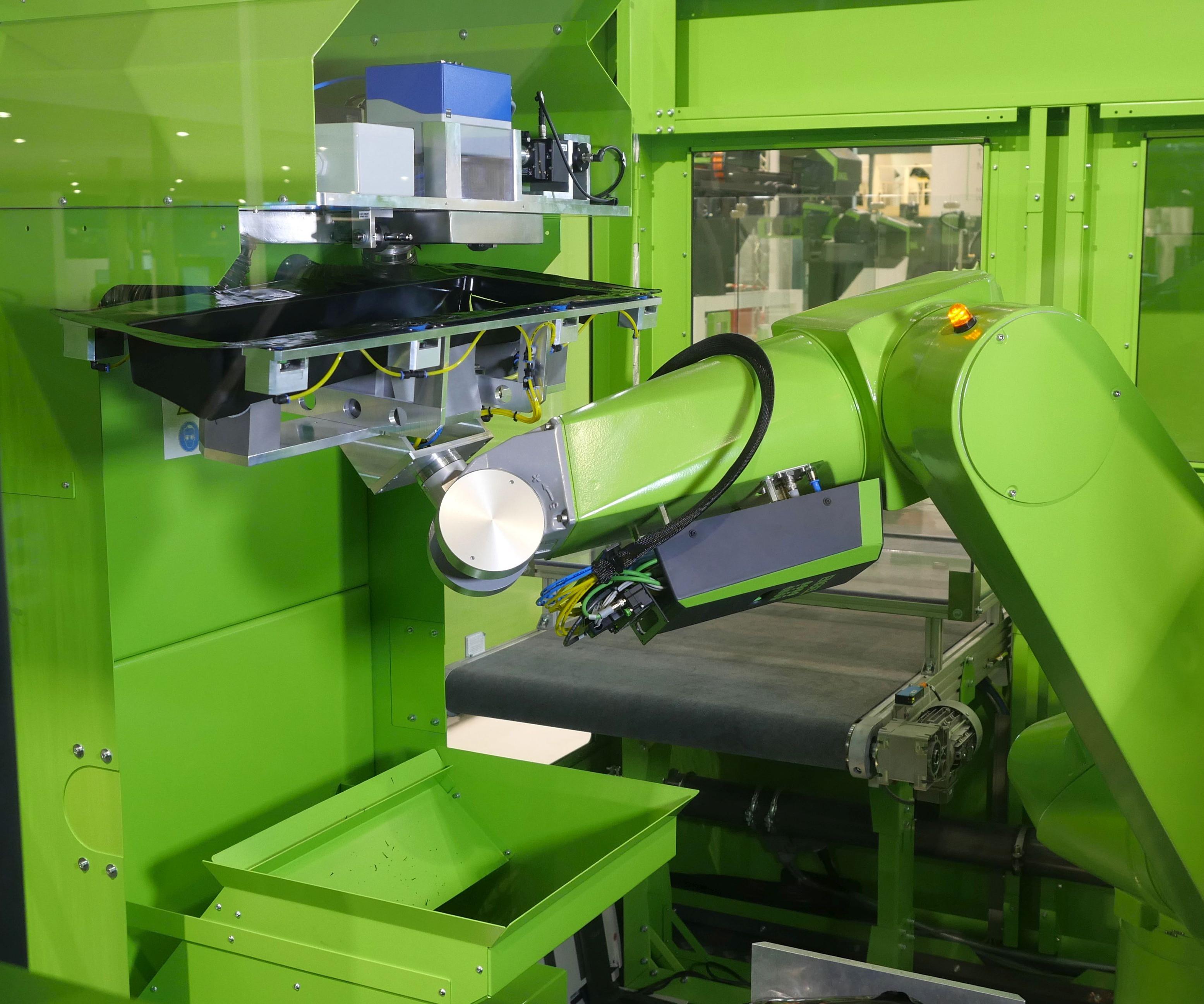 El robot multieje easix conduce el contorno del componente a lo largo del láser y seguidamente coloca el panel de puerta listo para montar en la cinta transportadora.