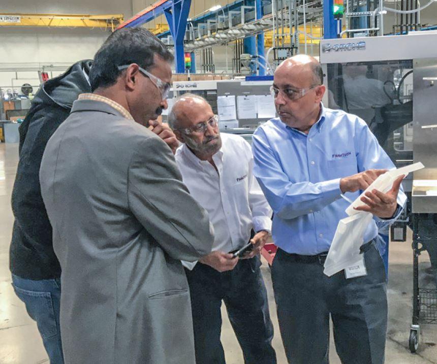 Suhas Kulkarni (derecha) instruye a los participantes durante un taller de DOE en la planta del moldeador personalizado Comar en California.