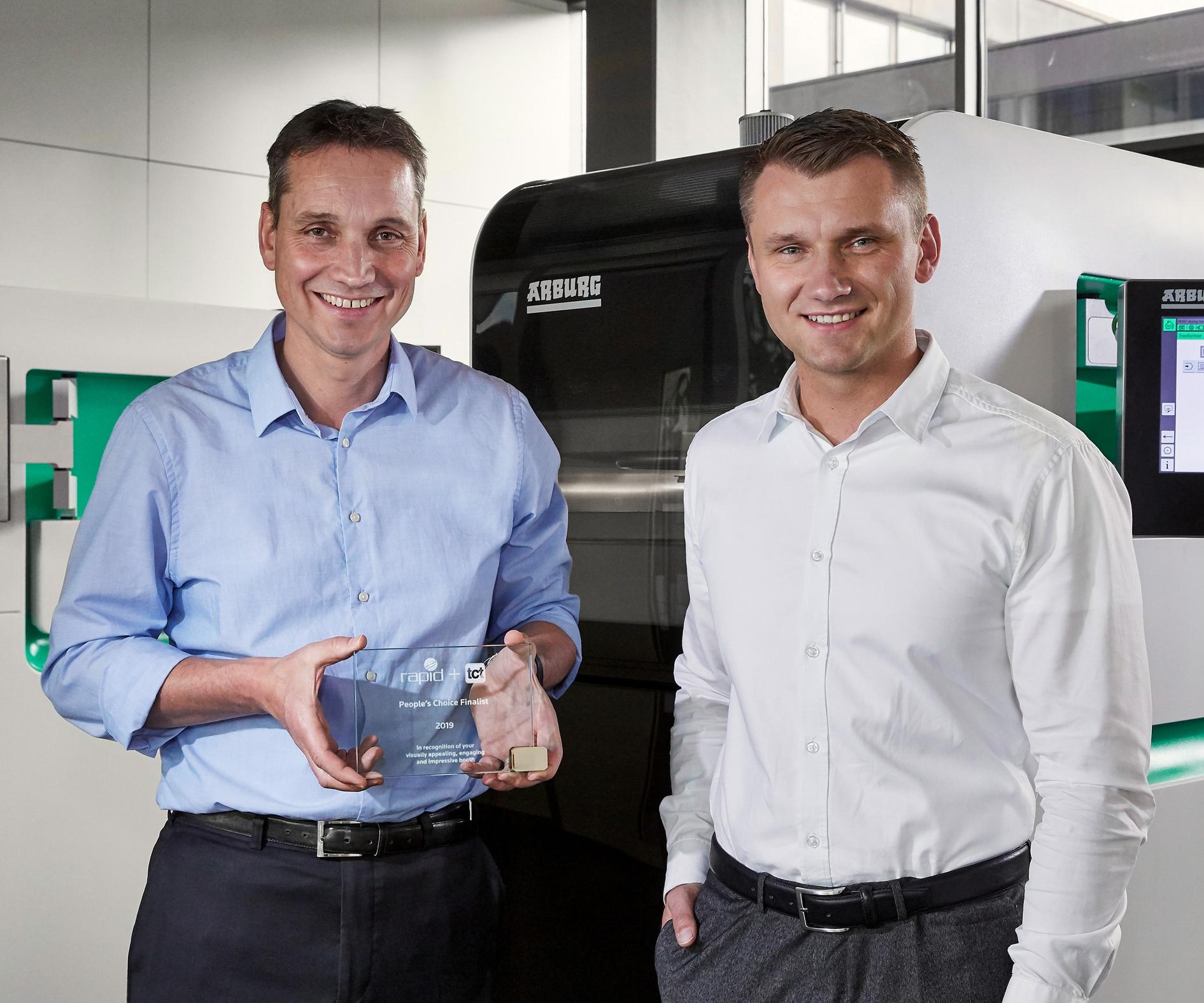 A la izquierda, Lukas Pawelczyk, responsable de ventas globales de Freeformer en Arburg; y Martin Neff, encargado del área de formado de plásticos con el premio otorgado por parte del público en la pasada Rapid + TCT 2019, realizada en Detroit (USA). Crédito: Arburg.