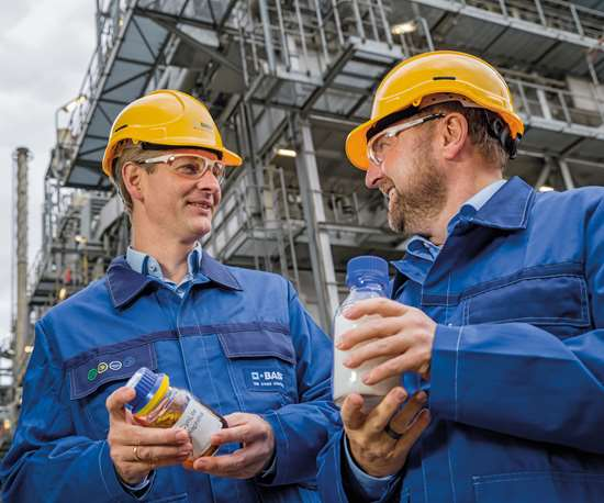 Dr. Stefan Gräter ay Dr. Andreas Kicherer con una muestra de aceite combustible de pirólisis y el plástico producido con él delante de una planta de craqueo a vapor.