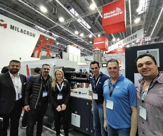 Representantes de Evco celebrán la compra de dos máquinas de moldeo por inyección eléctrica ROBOSHOT, en el stand de Milacron.