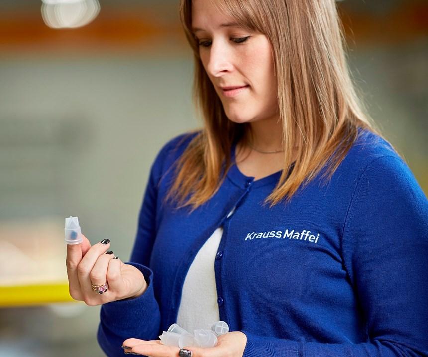 KraussMaffei employee holding dosing caps