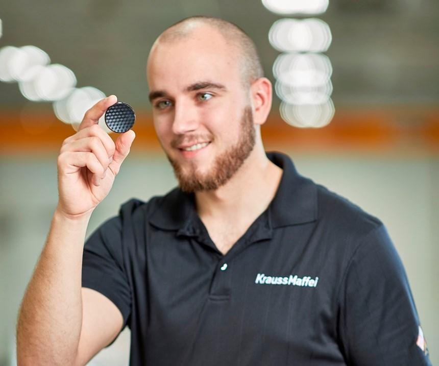 KraussMaffei employee holding a circular plastic part