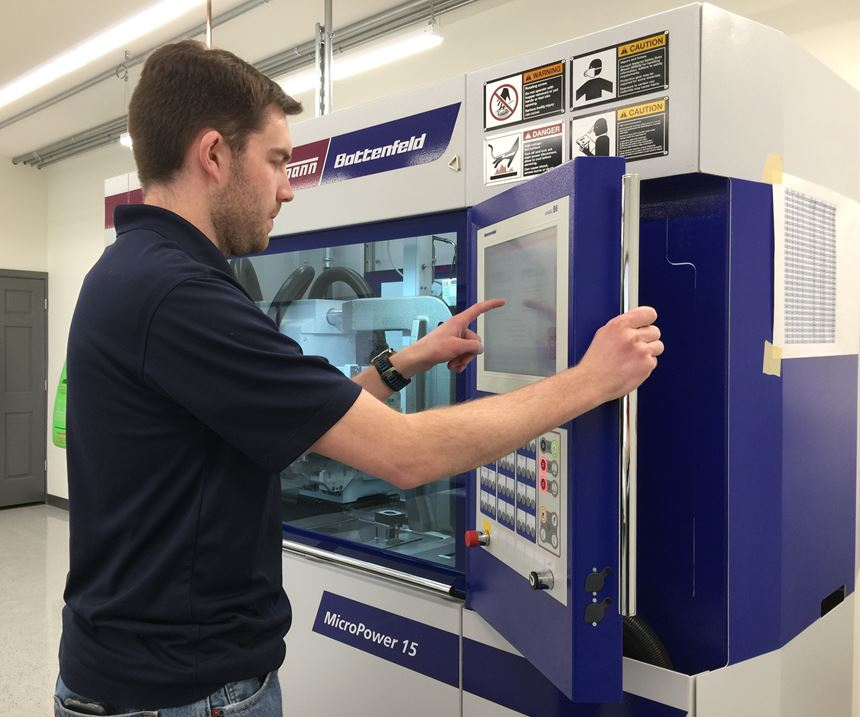 Person operating controls on Wittmann Battenfeld MicroPower 15-tpress.