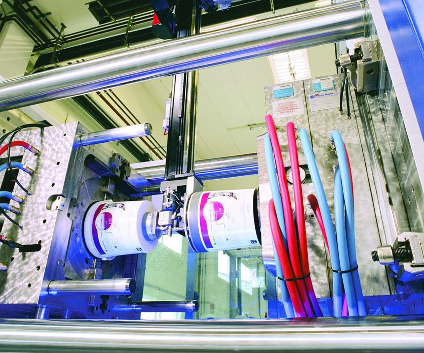 in-mold labeling (IML), which requires the robot to pick up labels from a dispensing station, deposit the labels in the cavities, and remove parts from the cores