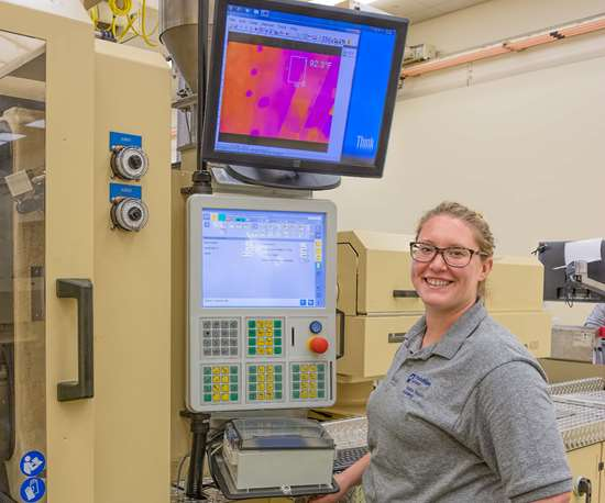 Plastikos medical molding manager Danielle Bentley with screen that shows Arburg ALS and RJG eDART data.