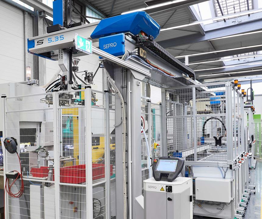 Two injection molding cells each include three Sepro linear robots operating together with Arburg vertical injection molding machines.