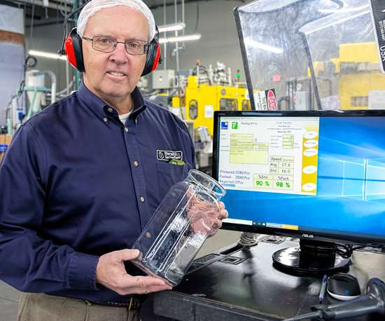 MSA president and CEO Mel O'Leary next to one of the CyFrame screens stationed throughout the plant that provide real-time production data to both machine operators and supervisors.