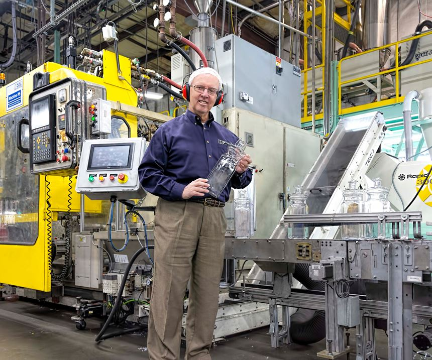 Meredith-Springfield president and CEO Mel O'Leary holds a large EPET jar molded on a Bekum extrusion blow molding machine