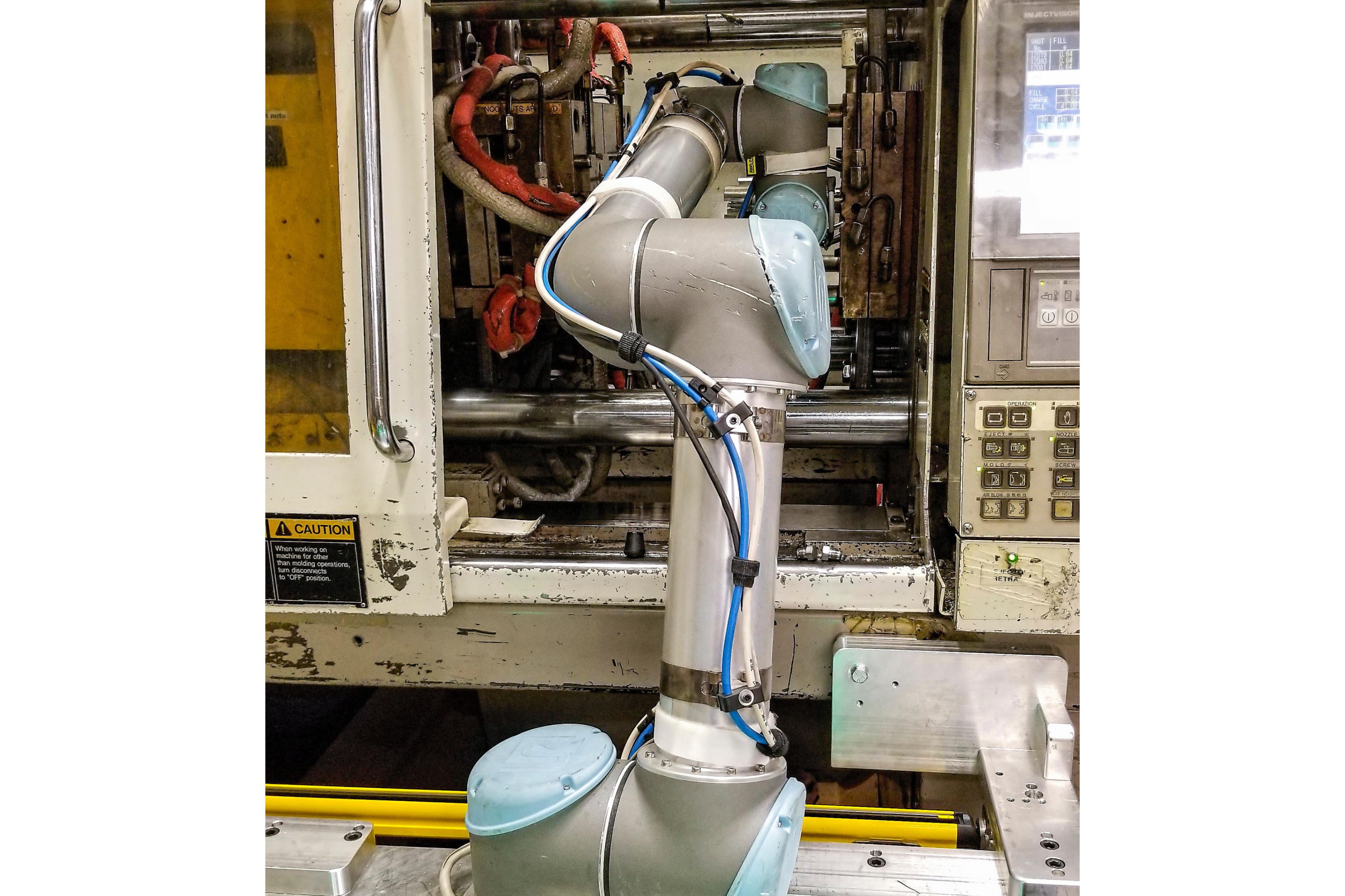 El cobot UR5 coloca dos insertos pequeños en el molde, luego extrae las piezas terminadas y el canal frío.