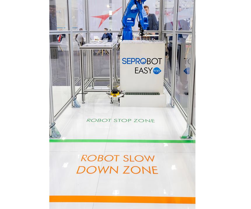 The SeproBot concept uses the speed and versatility of a conventional six-axis robot (or a Cartesian model), surrounded by physical guarding but giving operators safe access through openings protected by sensors, light curtains or other safety devices.