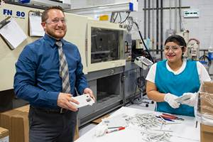 Instilling pride of workmanship is a top goal of Natech's in-house training programs. Here, head quality auditor Andrew Dunham examines electrical enclosure parts with operator Carla ____.