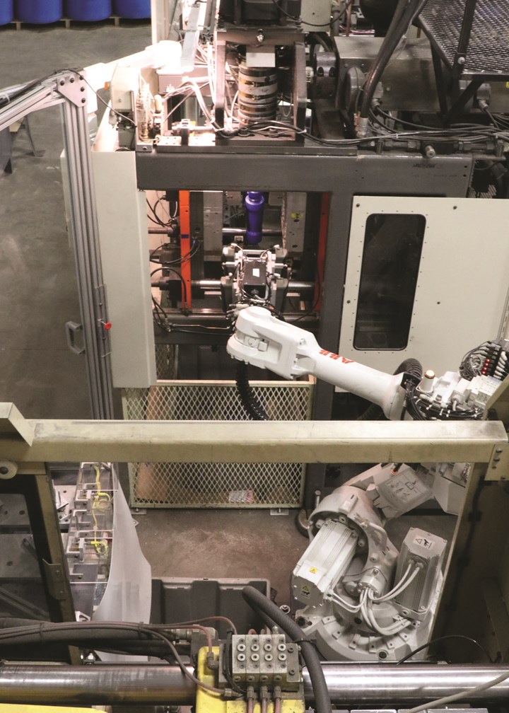 The six-axis robot waits by the blow mold for a second robot to remove the bottles for leak testing and trimming. This view is looking over the injection press, whose tiebar is seen at bottom.