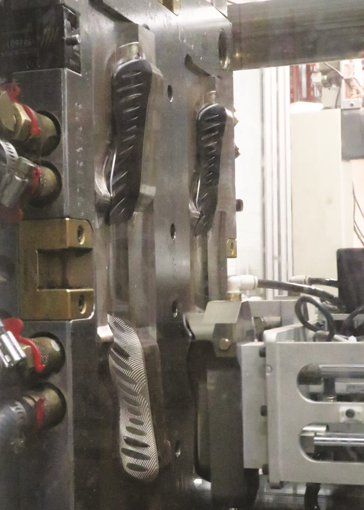 Four TPE soft grips are removed from the injection mold of a 120-ton press by a six-axis robot.