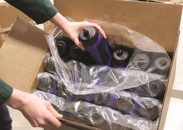 An operator touches the finished bottles only for a quick visual check, adding a cap and UPC label, and packing.