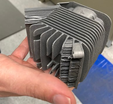 additive manufactured cylinder with support structures still visible