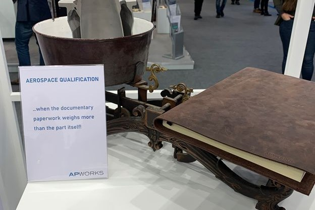 a scale showing an aerospace part that weighs less than a book