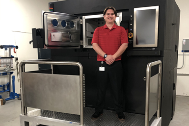 Zack Hopkins, an engineer at Chromalloy Gas Turbine, stands next to its Sapphire metal additive manufacturing system.