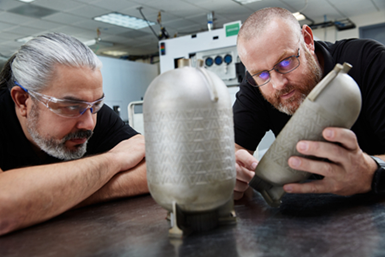 Engineers examine a titanium fuel tank printed on a Velo3D AM system with no internal supports. Similar tanks/pressure vessels are designed for use in aerospace and defense applications.