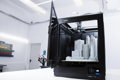 A photo of Zortrax's M300 Plus 3D printer, with a city model on the build plate