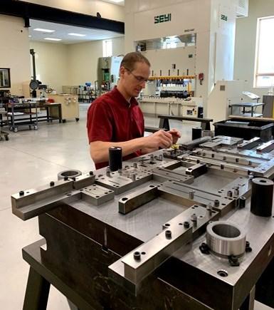 Craig Dohe, el hermano de Neil, también trabaja en Dies Plus como fabricante de herramentales y matrices. Aquí, él trabaja en el ajuste final de los componentes del troquel. Una nueva prensa Seyi y un puente grúa también ocupan el cuarto de herramentales.