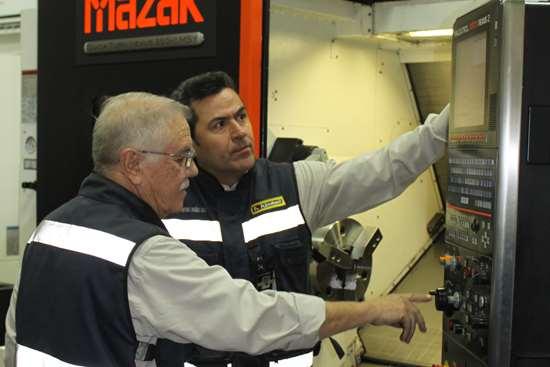 """Arturo Dueñes, Director de Kimball, (derecha) revisa la programación del mecanizado junto con su Jefe de Taller, Mateo Yáñez. Para el ingeniero Dueñes es muy importante la facilidad en la programación de la máquina: """"El software Mazatrol es sumamente amigable y, junto con los controles Mazatrol, permiten 'jugar' para bajar tiempos de mecanizado""""."""