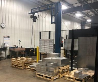 La carga y descarga de partes son las tareas principales del operador del sistema de manufactura flexible. Un tablero de prioridad cerca de la estación de descarga enumera los próximos trabajos.