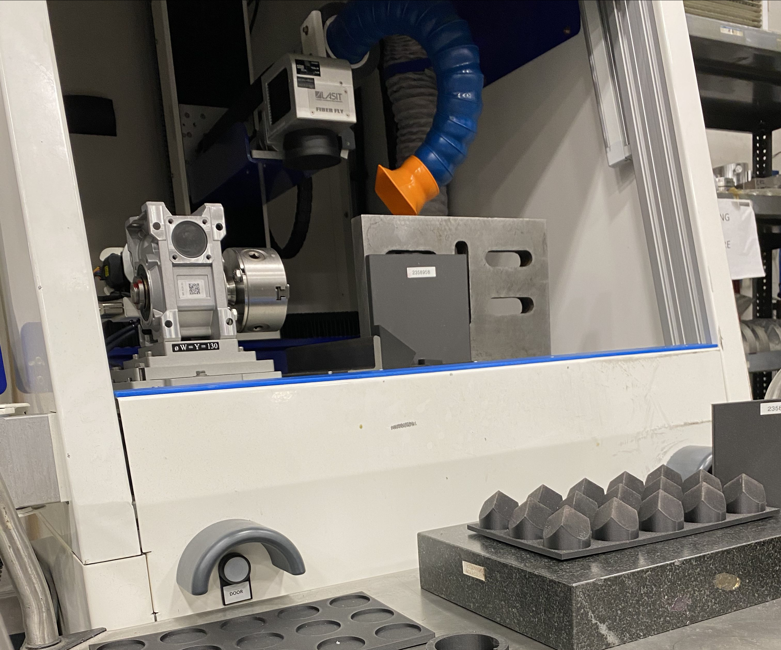 3D-printed fixtures for CNC machined parts are arrayed in front of a part-marking machine at Advanced Precision Engineering (APE).