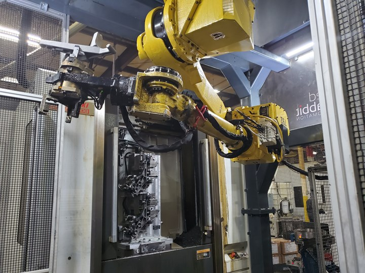 A robot hangs upside down from a frame to service multiple CNC machine tools.