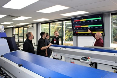 A photo of Jim Langlois leading the J&W Swiss team through the previous day's production records on Datanomix Fusion