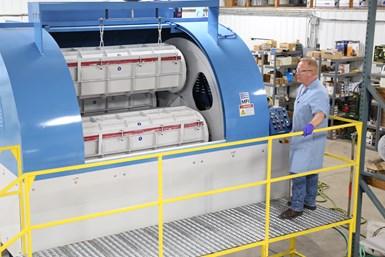 Las máquinas de volteo de barriles vienen en muchos tamaños para adaptarse a partes grandes y pequeñas. Tom Mathisen, quien aparece en la foto, supervisa esta máquina en el laboratorio de la empresa, donde ayuda a desarrollar procesos para los usuarios.