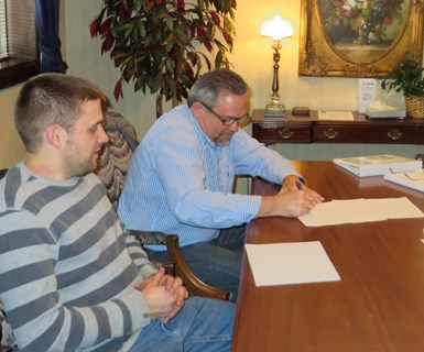 Tyler VanRee and his dad sign ownership transition documents