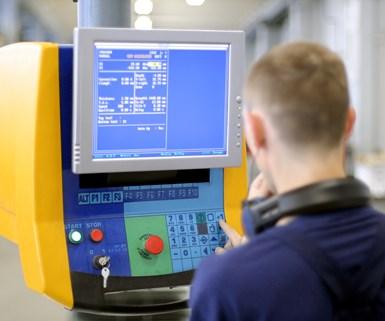 an operator facing a CNC screen