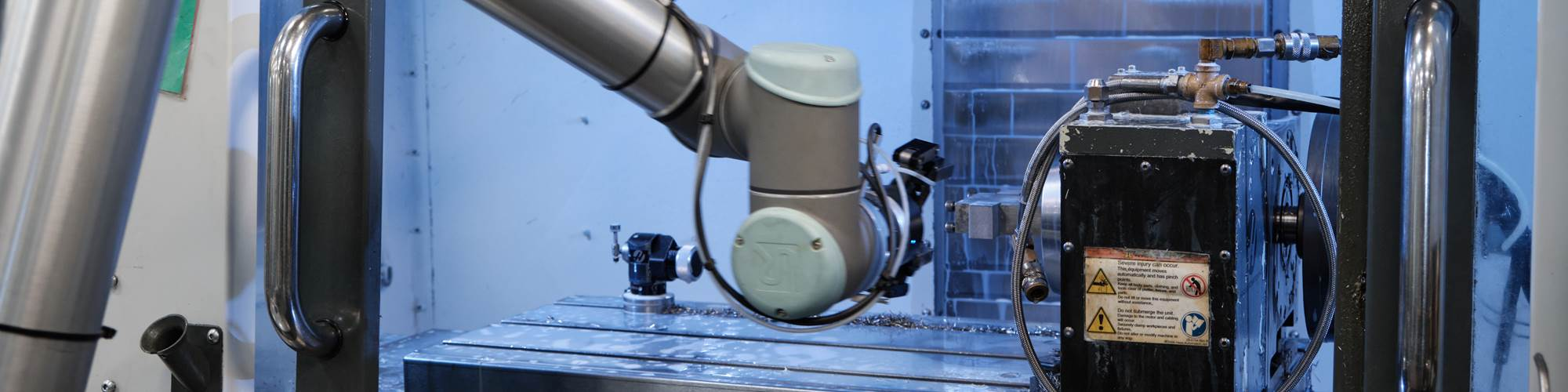 A collaborative robot loads a quick-change fixture into a machine tool at Rimeco Products.